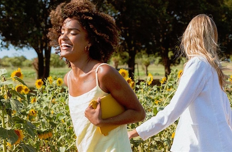 Two woman run in a field of sunflowers smiling and laughing.