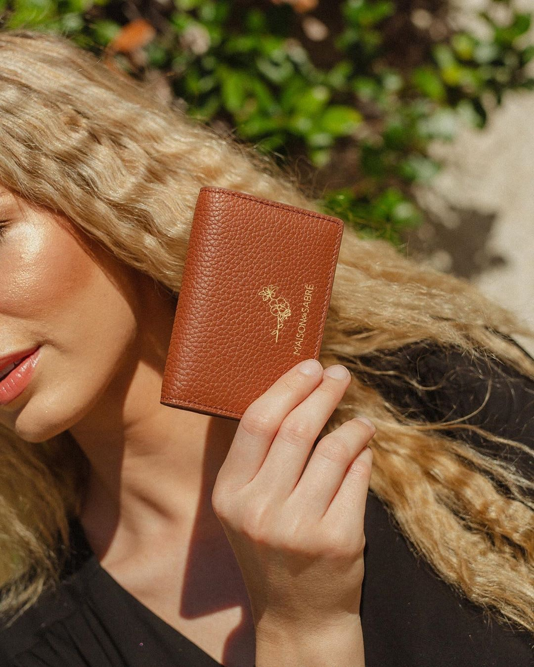 A blonde woman holds a stunning brown wallet up to the sun.