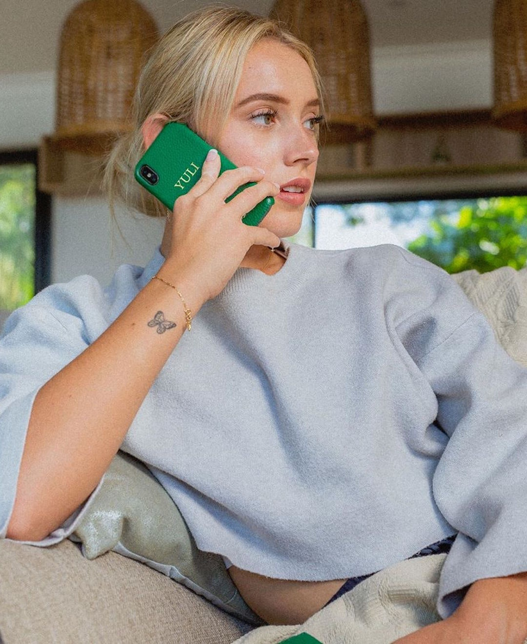A blonde woman sits on the couch and holds an iPhone to her ear.