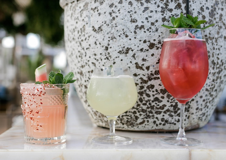 three cocktails sitting on a bench in front of a pot.