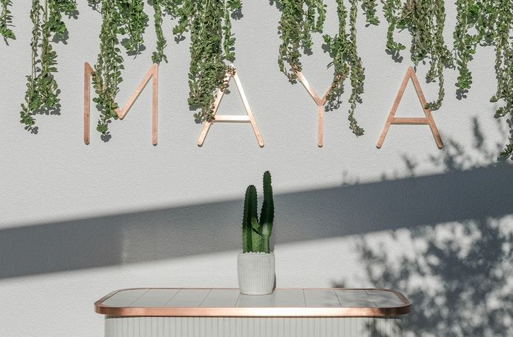 A gold sign saying Maya on a white wall.