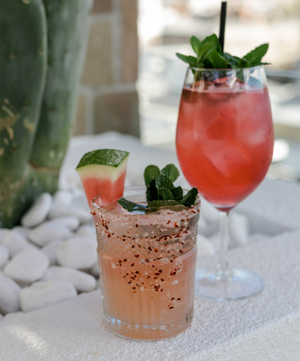 A pink spritz and a watermelon margarita with a city skyline visible behind.