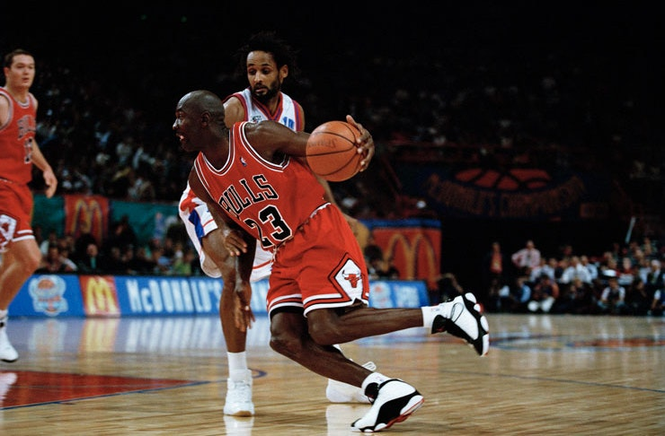 Michael Jordan, in his iconic red Chicago Bulls jersey and Nike Air Jordans, ducking and weaving on the court.