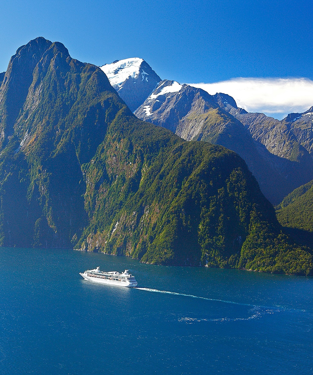 A boat travels down the pass at Milford Sound with stunning scenery.
