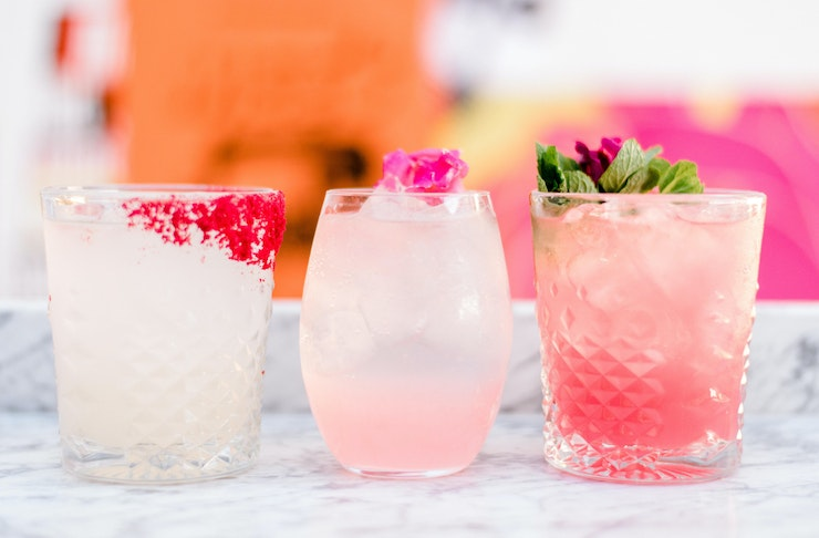 Three pink coloured cocktails lined up at the bar at Miss Mee on the Gold Coast.