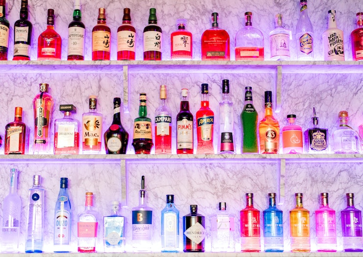 Three bar shelves are lined with many liquor bottles.