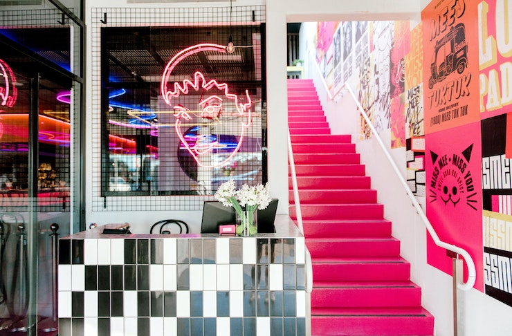 A hot pink staircase connects the two levels at Miss Mee on the Gold Coast.