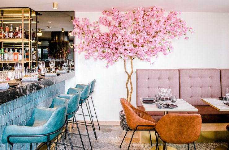 The elegant interior of Mr. in Nobby Beach, featuring a plush soft pink bench seat and velvet blue bar stools.