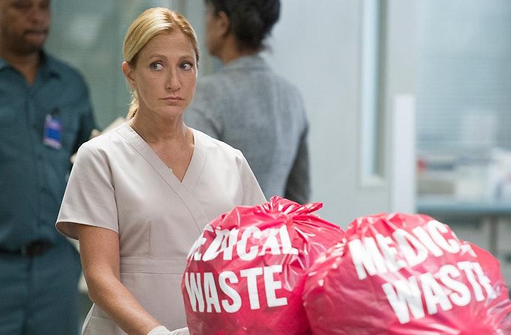 Edie Falco as Nurse Jackie looking suspicious as she disposes medical waste