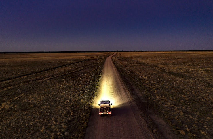 A car drives on a dusty desert road beneath a canopy of stars.