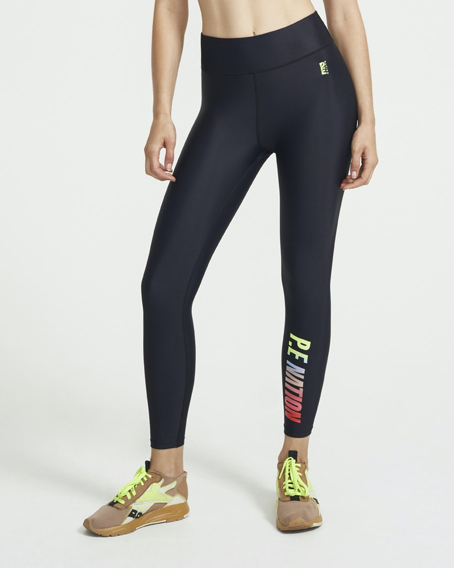 A woman stands athletically posing in P.E. Nation Emerging Leggings, a crop top, and colourful sneakers.