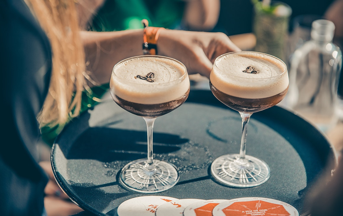 A girl carries a couple of Parasol & Swing's legendary espresso martinis outside onto the deck.