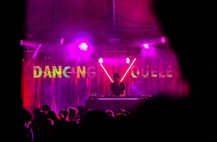 A nightclub scene with a pink lit back wall with the words dancing queen and a DJ