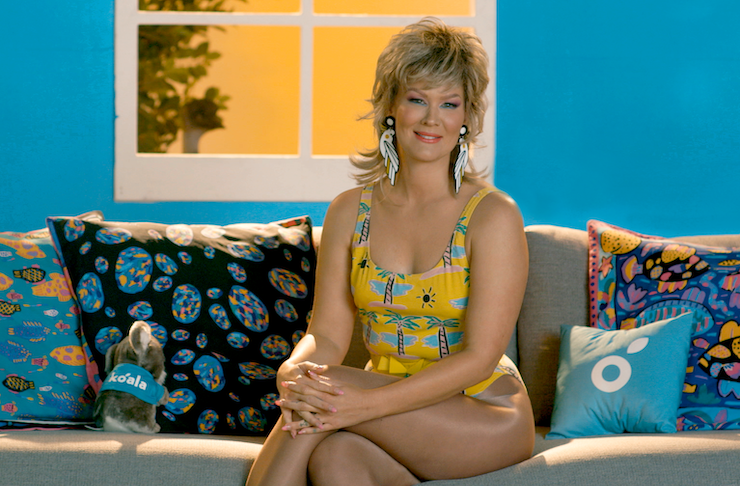 A woman dressed up in 80s aerobics clothes sits with legs crossed on a couch.
