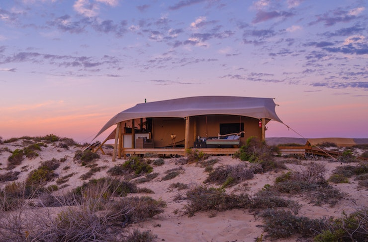 A bell tent sits on a sandy beach horizon at sunset.