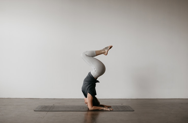 A woman in a grey room does a headstand on a yoga mat