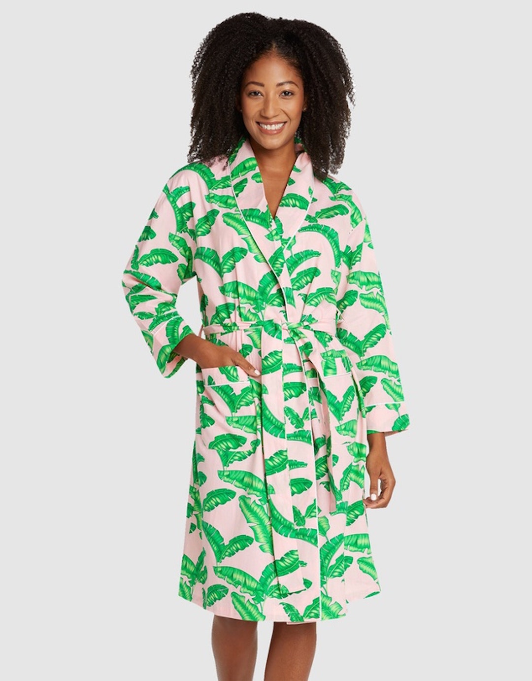A woman smiles wearing a dressing gown with a palm tree print.