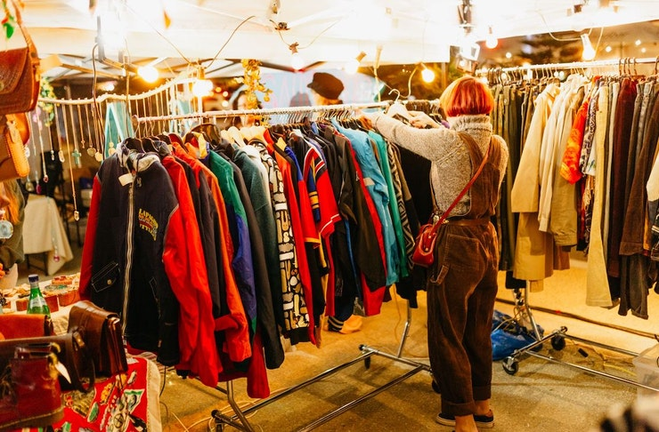 A girl looks through a rack of clothes at a market stall