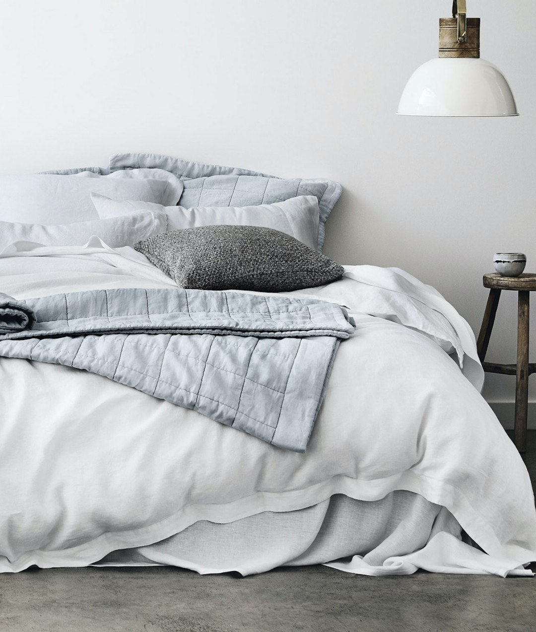 A cosy bed littered with white and blue quilts and sheets.