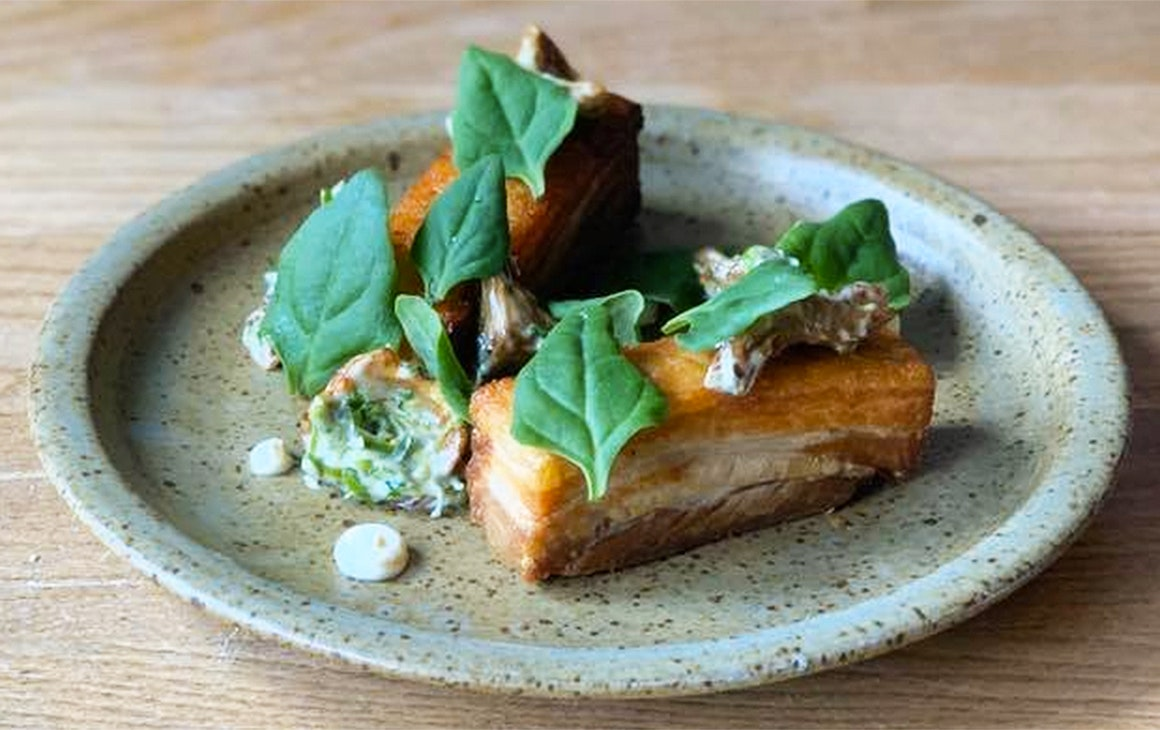 Delicious looking pork belly topped with green leaves sits on a plate at Sherwood.
