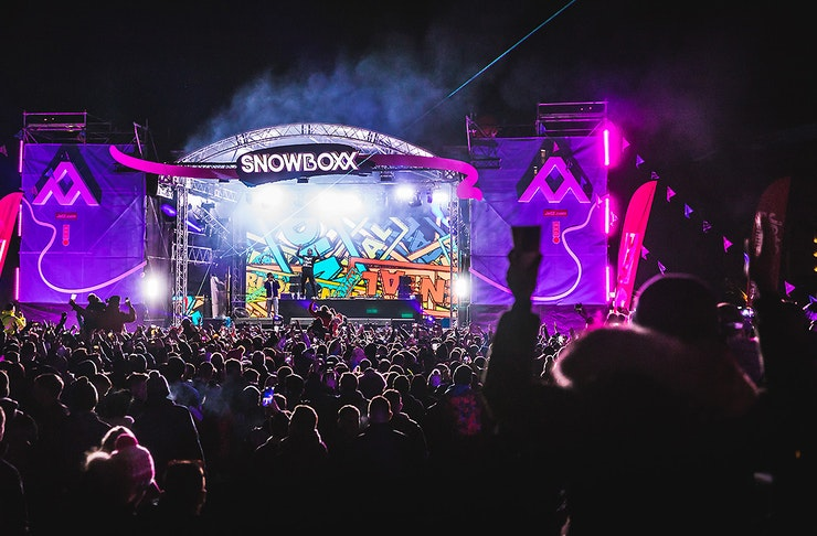 Snowboxx festival stage at night time with revellers enjoying the show.