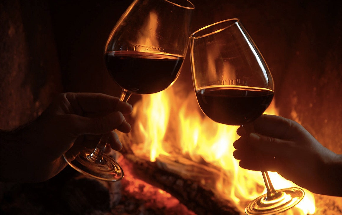 A couple cheers their red wine glasses in front of a roaring fire at Stafford Road Wine Bar.