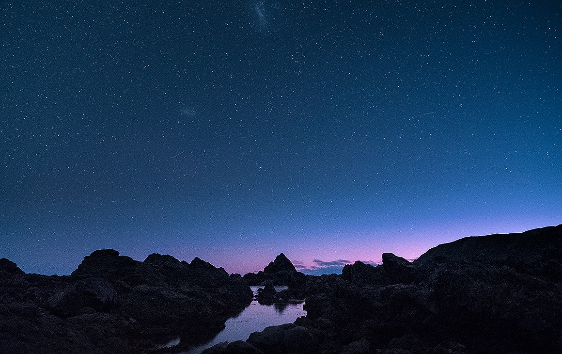 Otherworldly-looking rocks and water underneath a brilliant star-lit sky. One of the best places to stargaze in Wellington.