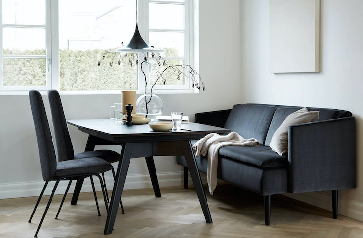 Navy chairs and a plush couch surround a black chic table.