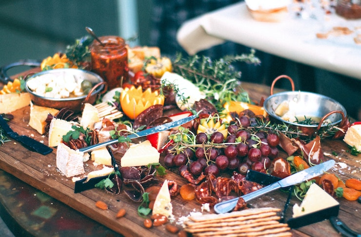 A messy spread of cheese, meat, fruit, dips and other goodies lays on a wooden table.