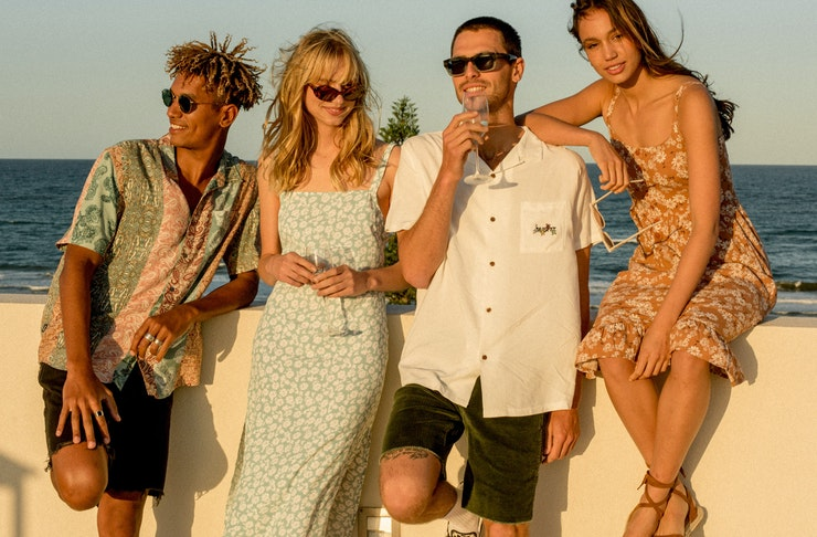 Two women and two men stand by the beach wearing chic coastal wear.