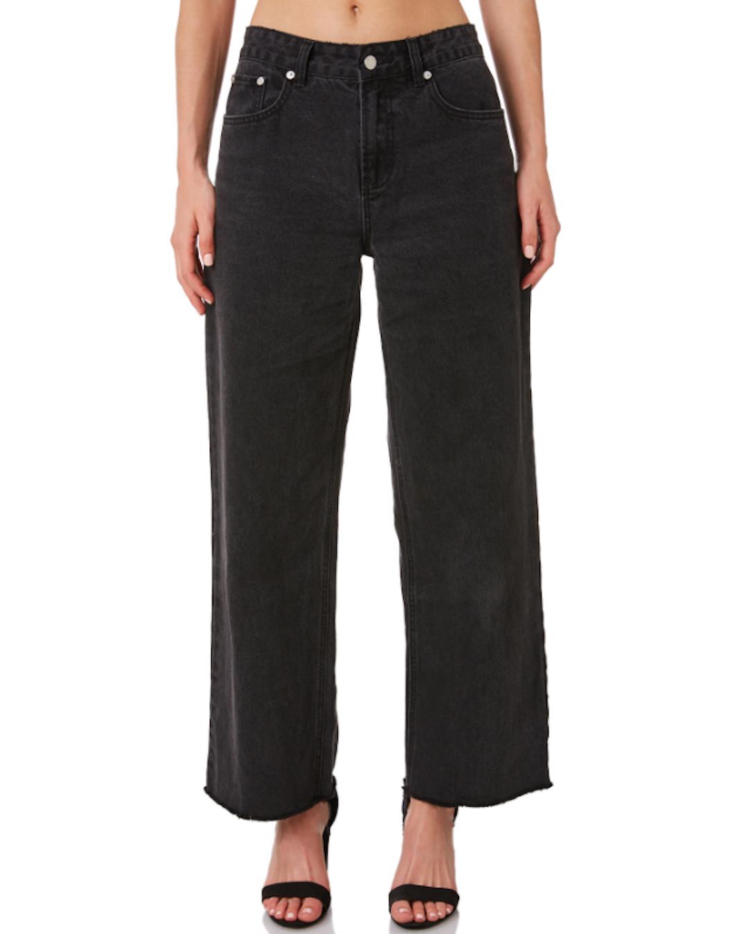 A woman wears black baggy high-waisted jeans.