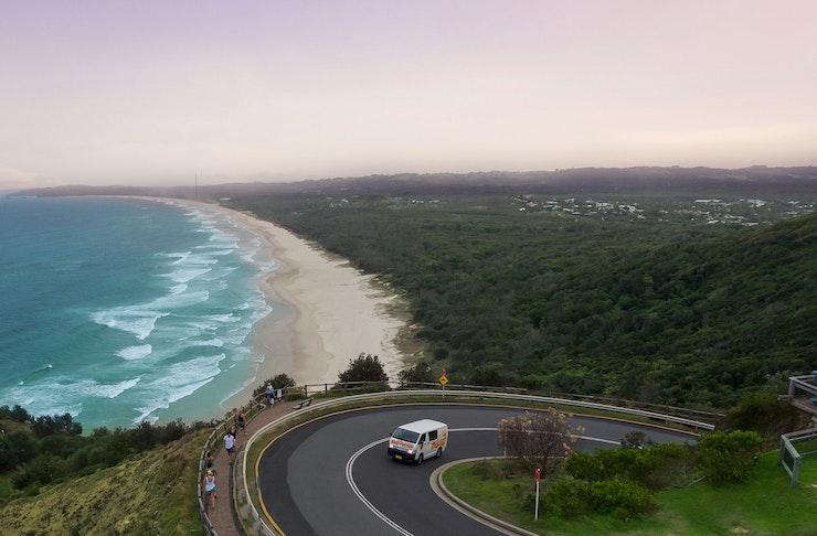 A campervan drives along a winding coastal road