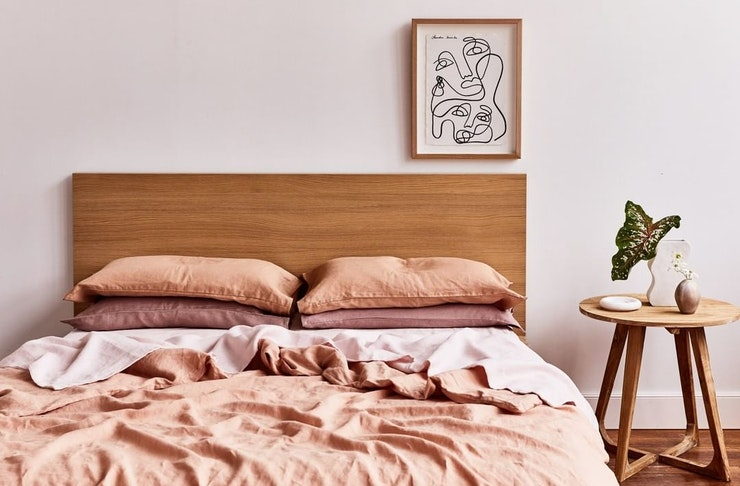 Pink and orange linen sheets lay sprawled on a bed with a wooden frame.