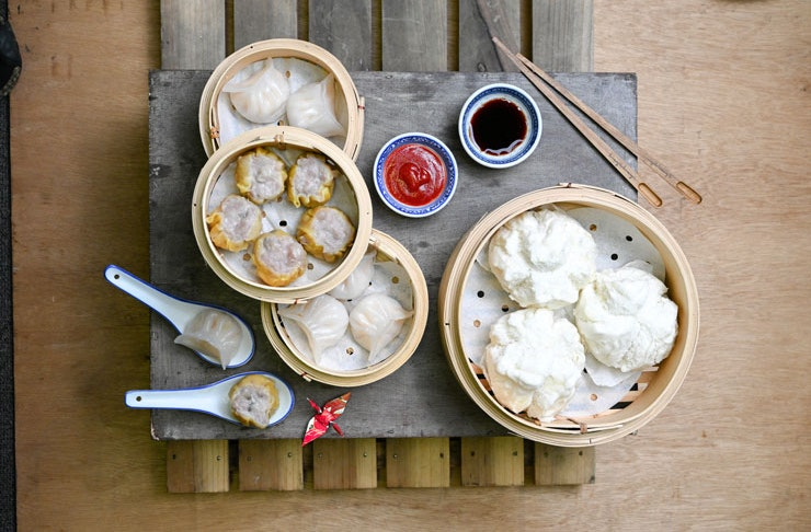 A top-down view of some yum cha, dumplings and pork buns with sauces and chopsticks to the side.