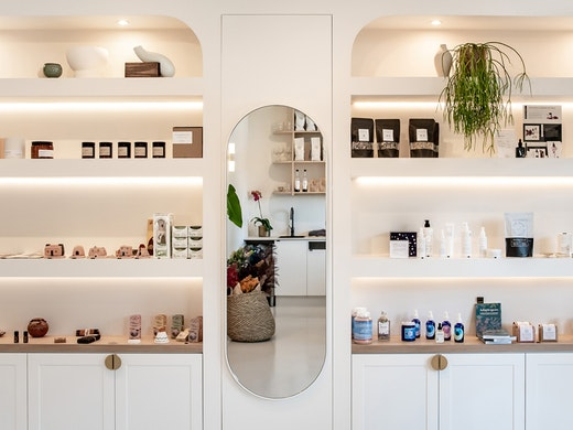 White custom-made shelves are stocked with beauty and wellness products at new Noosa store, The Orangerie.