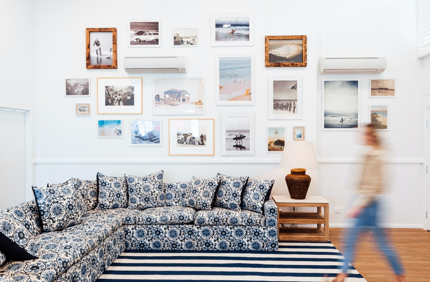 A blue and white l-shape couch sits in front of a gallery-style wall in a Byron Bay hostel.