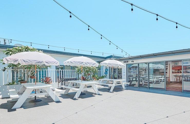The rooftop bar, kitted out with picnic tables and beach umbrellas, at Byron Bay's The Surf House.