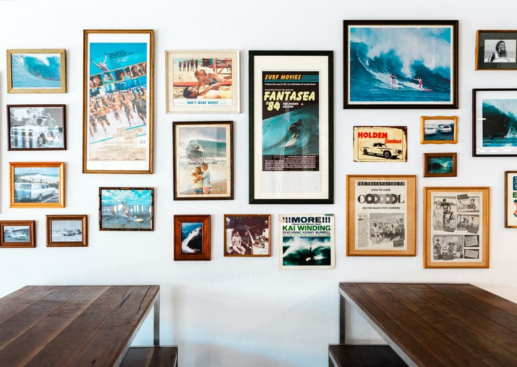 Two timber bar tables sit in front of a gallery wall featuring old surfing images.