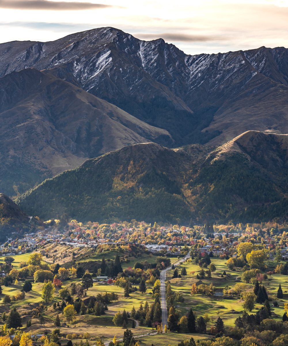 The quiet, green town of Arrowtown perched under snowcapped mountains