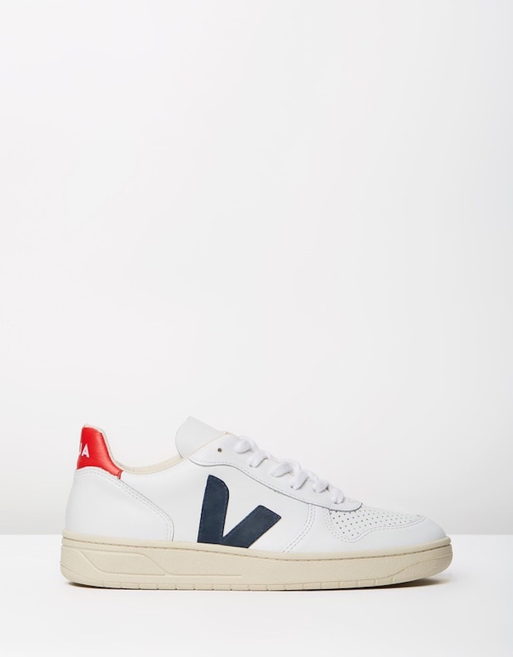 A single white sneaker with blue and red accents.