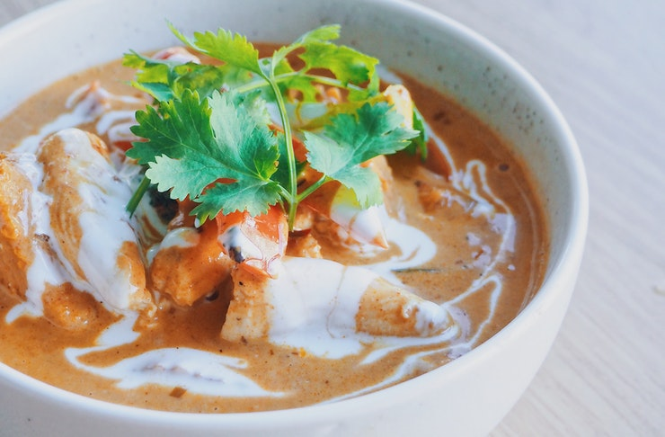A bowl of mouthwatering orange curry sits on a table waiting  to be devoured.