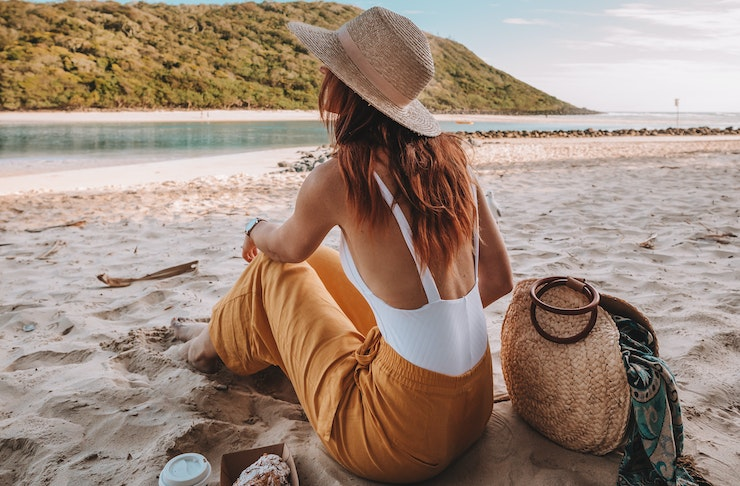 A woman sits on a white sandy beach next to a coffee and croissant.