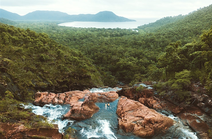 Two people wade at the edge of a waterfall overlooking lush rainforest.