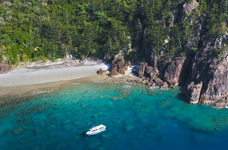 A boat is anchored in secluded cove.