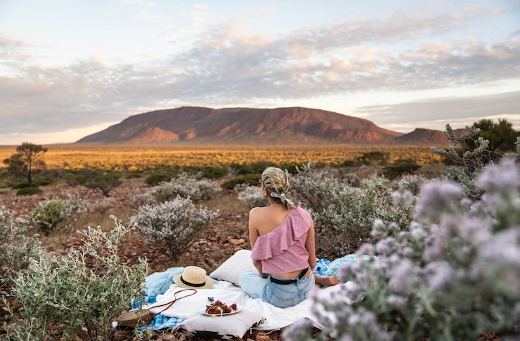 A woman sits on a picnic blanket as she gazes out towards the Western Australian outback.