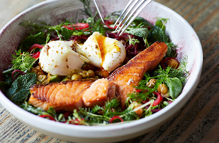A bowl of salad with grilled salmon and two poached eggs on top.
