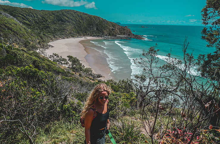 Young woman standing on mountain overlooking one of Byron Bay's beaches.