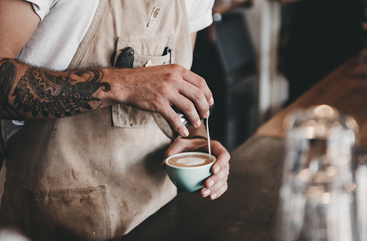 A tattooed male barista holding a coffee while pouring milk into the cup.