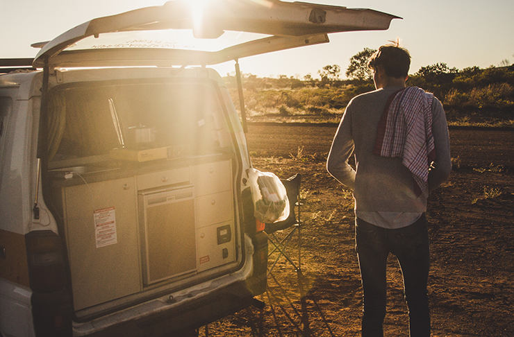 A man standing by his van, parked on the side of the road under the hot Australian sun.