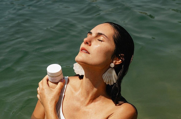A woman poses in the ocean with a bottle of Bache de Mar serum.